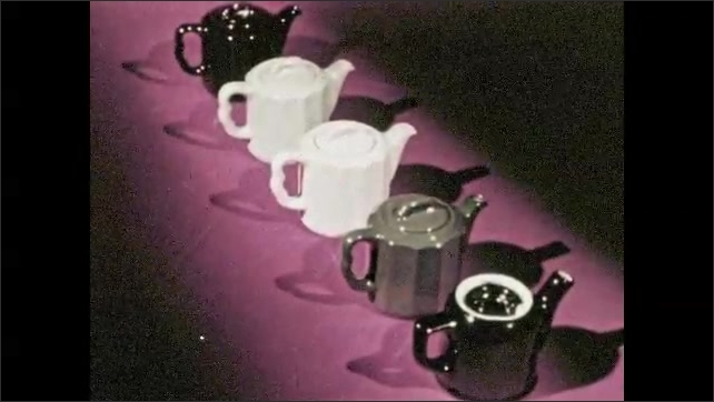1960s: Ceramic cream and sauce cups are laid out on table. Ceramic tea pots lined in row. Various ceramic cookware on table.