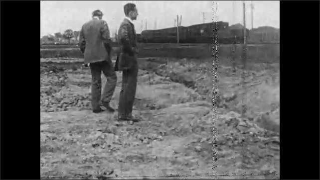 1920s: Tanks roll across terrain. Men in suits wander on field. Soldiers and men right overturned tank. Tank runs into fence and flips over.