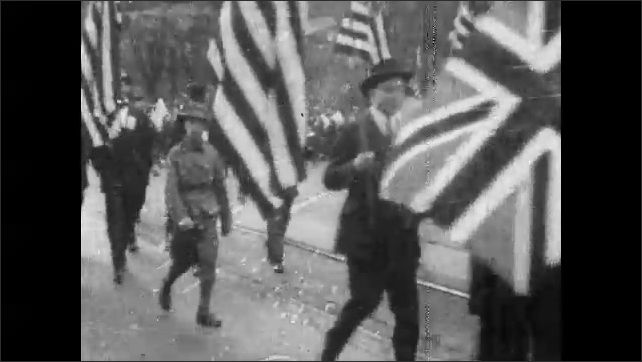 1920s: Soldiers and men walk around tank in demolished home. Men carry flags and banners in parade.