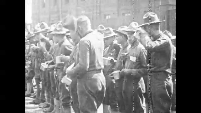 1920s: Young soldiers lounge on train car. Soldiers wave from train cars. Soldiers drink coffee from canteen cups. Military band plays at train station. Families embrace and say goodbye to soldiers.