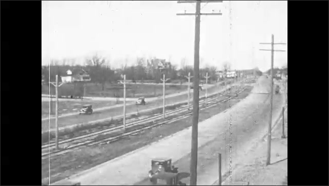 1920s: Men construct roads with shovels and bucket cranes. Cars drive along concrete roads and highways. Car drives over railroad track. Model T drives down steep gully.