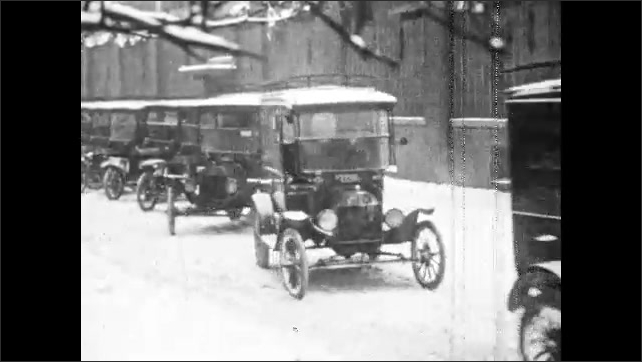 1920s: Postal worker loads boxes onto mail truck. Model T trucks pull away from parking area. Cars drive along winding mountain road.