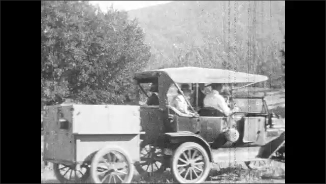 1920s: Cars drive through redwood forest. Man in car pets bear in national park. Men and women exit car and set up pop-up camper tent.