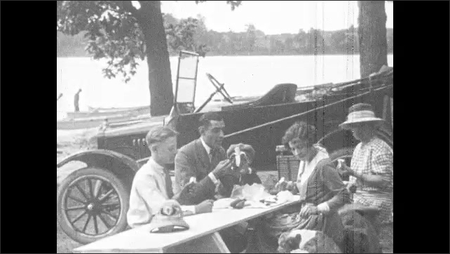 1920s: Men and women enjoy picnic under camper tent. Family picnics in park. Family and dog picnic near lake. Women pick flowers in field near car. Men remove seats from Model T and sleep in car.