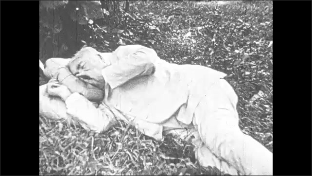 1920s: Henry Ford chops wood as other men cook and film campsite. Men read newspapers at camp. Thomas Edison naps on lawn at campsite. Harvey Firestone chops wood with Ford.