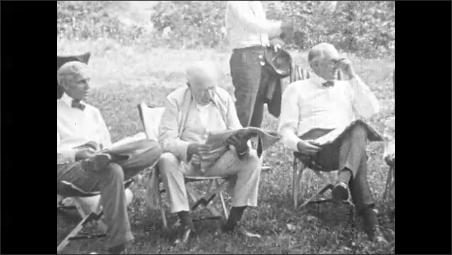 1920s: Harvey Firestone chops wood with Henry Ford. President Harding chops wood with axe. Ford, Edison and Harding read newspapers in chairs at camp. Men shake hands and talk near farm tractor.
