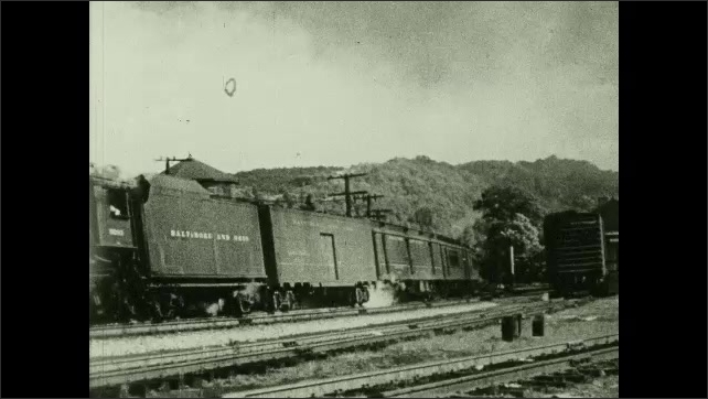 1950s: UNITED STATES: train leaves depot. Steam above train. Carriages from side view.