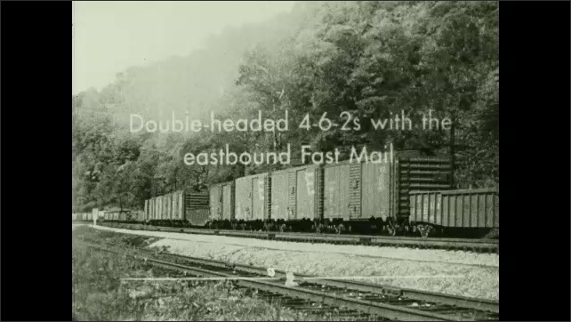 1950s: UNITED STATES: 2-8-8-4 Yellowstone type locomotive works as pusher. Title. Train pushes carriages along tracks. Double-headed 4-6-2s with eastbound Fast Mail. Ground view of travelling train.
