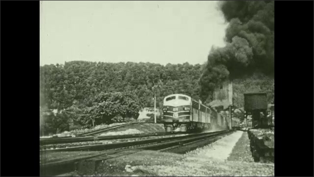 1950s: UNITED STATES: 3-unit Electro-Motive diesel and 2-8-8-4 get underway at coal chute between Garrett and Meyersdale. Title. Smoke above train.