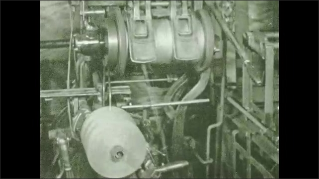 1930s: Fibers travel through spinning machine. Woman opens cover on machine, fibers spin on large bobbin. Machine wraps fibers into ball of twine.
