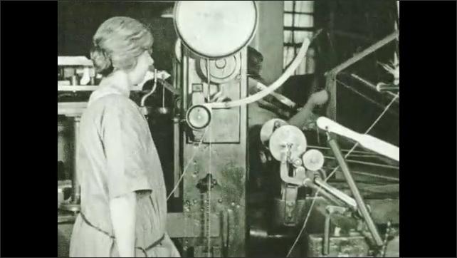 1930s: Woman runs strands of twine through stress test. Man cuts fabric.