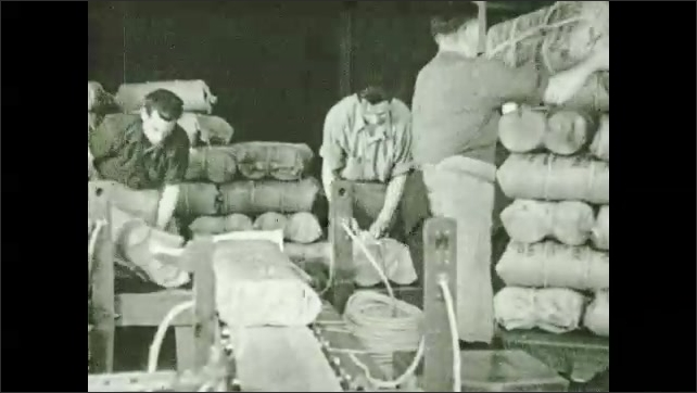 1930s: Men tie up bags of twine. Man loads bags of twine onto chute. Man unloads bags at end of chute, stacks up bags.