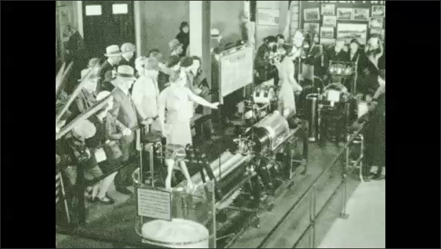 1930s: People hather around twine production exhibit, woman points out equipment.