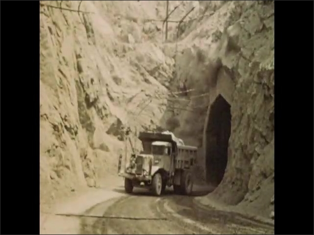 1950s: Cement plant on open face quarry. Cement plant near deep mine. Dump truck exits tunnel. Bucket crane lifts clay. Bucket crane swings over body of water. Bucket crane plunges into water.