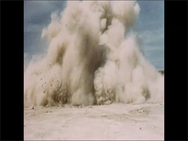 1950s: Men wire explosives at quarry. Men lower explosive into drilled hole. Fingers push buttons. Quarry face explodes. Rock and debris on quarry floor.