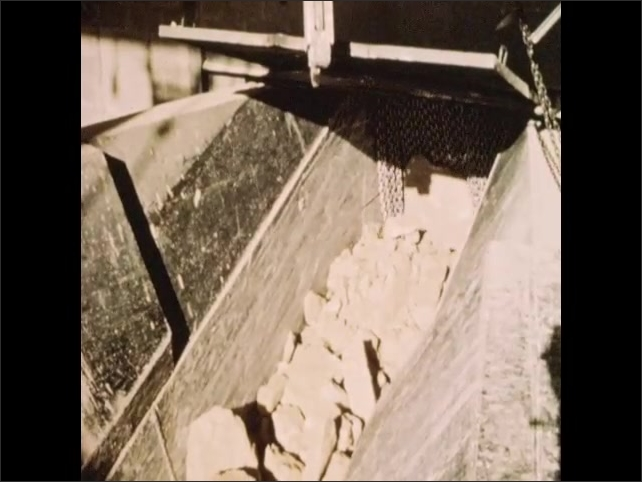 1950s: Dump truck pulls up to crushing facility. Truck dumps rocks into underground crusher. Rocks move along conveyor belt to crusher. Crushed rocks fall into secondary crusher.