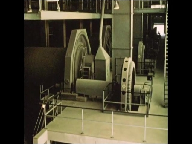 1950s: Large metal wheels turn tumblers. Industrial tumblers spin. Hand taps beaker as ground material falls into pile.