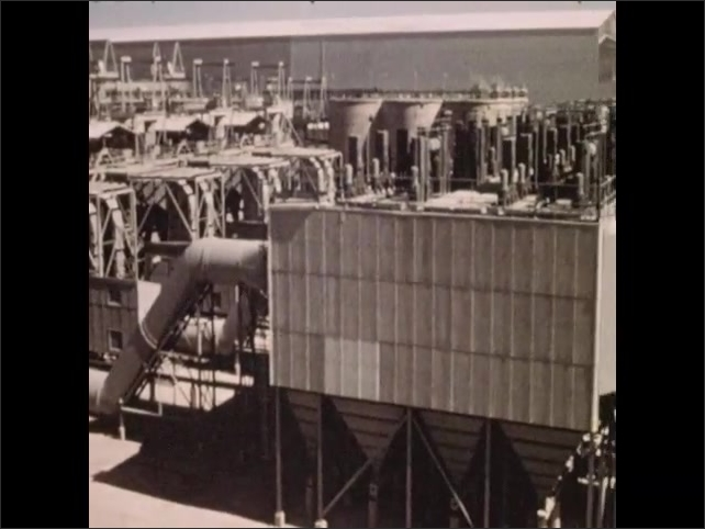 1950s: Clinkers tumble in cooling device. Exterior stacks at rotary kiln facility. Electrostatic condensers. Smokestacks release heat and steam into the air.