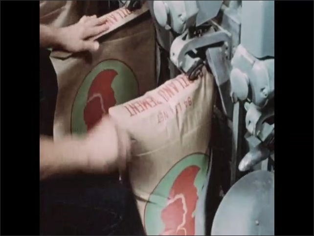 1950s: Man attaches bags to machinery. Bags fill with cement. Bags drop away from machine after filling.