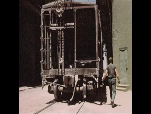 1950s: Hands demonstrate valve insertion in cement bag. Man attaches bags to cement filler machine. Man rides train car toward industrial cement silo. Flexible loader lowers onto train car.