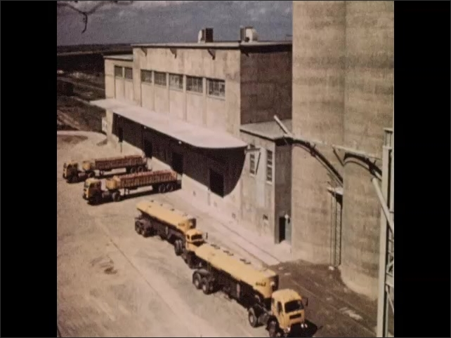 1950s: Industrial cement storage silo. Transport trucks parked around cement silo. Transport truck fills with cement.