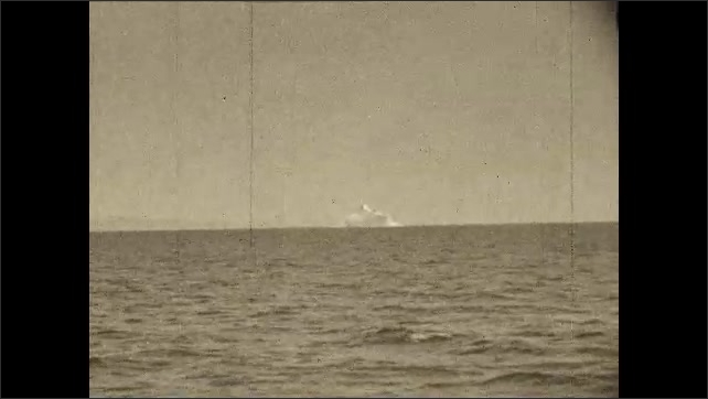 1930s: Sailor on deck of boat looks through sextant. Boat goes by iceberg in distance. Iceberg. Boat travels by iceberg.