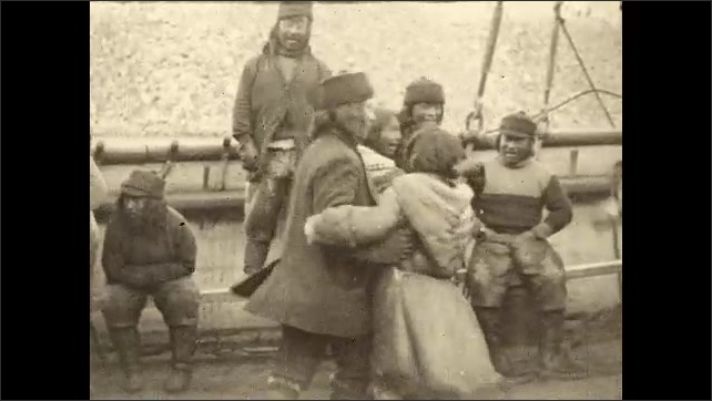 1930s: Men and women, wearing furs, are dancing on deck of ship in arctic.