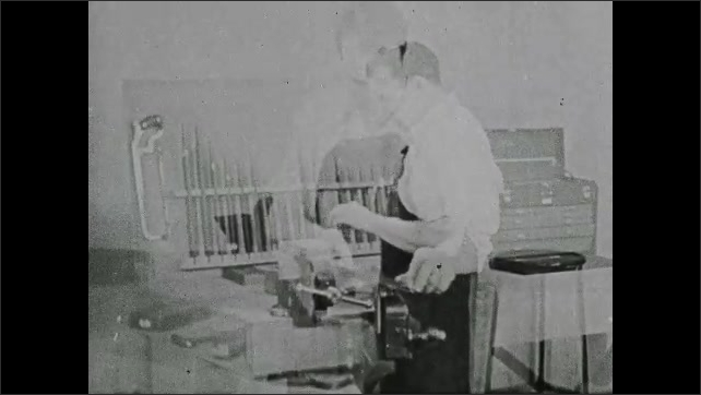 1940s: UNITED STATES: machine shop work. Workers in factory. Bench work. Man files at work bench. Man uses hand file.