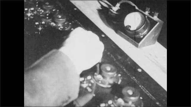 1930s: Man adjusts recording equipment. Hand turn knob. Close up, recorder making record.