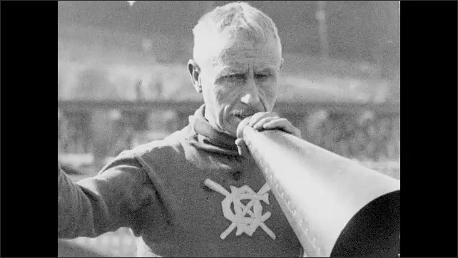 1930s: A man with a megaphone stands on the dock with spectators. He calls to two crew teams in the water and fires a pistol. They race.