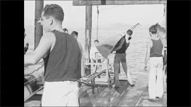 1930s: Two crew teams race through the water. On the dock, team member lift singles boat and carry them to the water.