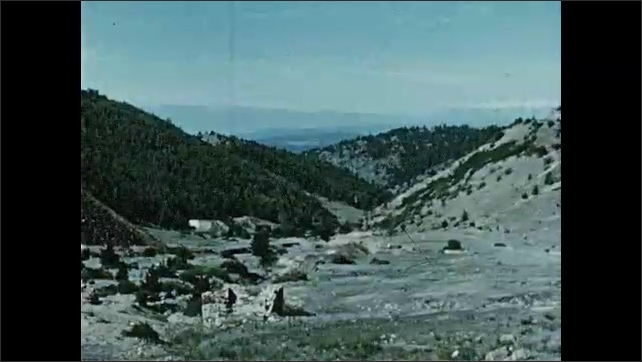 1950s: Old mining town buildings. Cow stands by building. High desert mountains. Brick ruins.