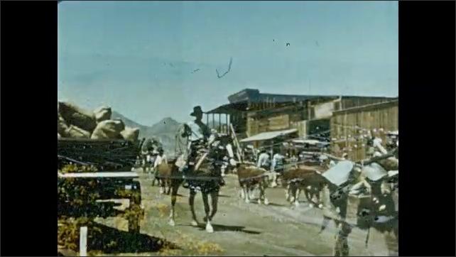 1950s: Old wooden building. Desert landscape. Small desert town. Men ride on horseback, herd cattle. Covered wagon rolls down street. Women cross street.