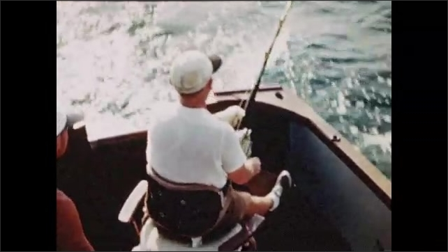 1950s: Water, tuna fishing boat, man sits, wears waist belt harness fishing rod, leans forward, reels in line, rotates seat. Man leans over, pulls line.