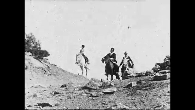 1920s: ARABIA: man and goats travel down river. Donkey in river crossing. Goat stands on donkey. Boy and men on horses. View across mountains