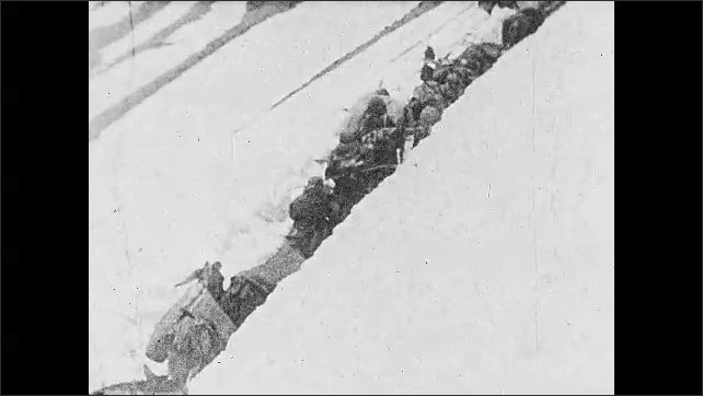 1920s: ARABIA: nomads cross over mountain with animal. Man plays music on back of donkey. Men lead animals up snow bank.