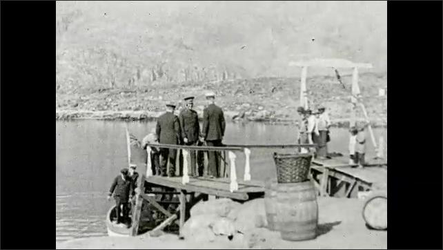 1930s: GREENLAND: men in uniform arrive at jetty.