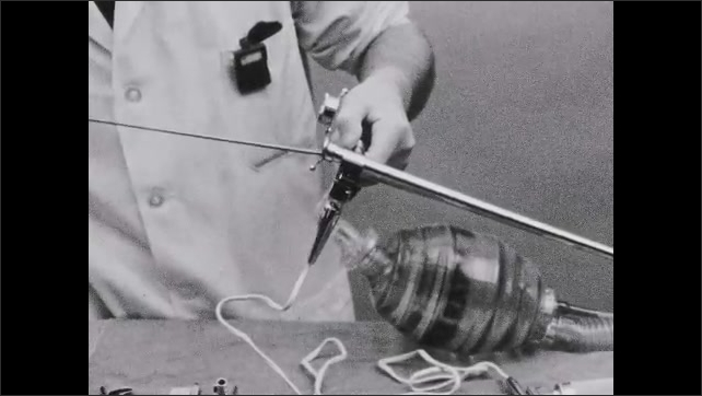 1950s: UNITED STATES: fingers squeeze bag. Man inserts metal into pipe.
