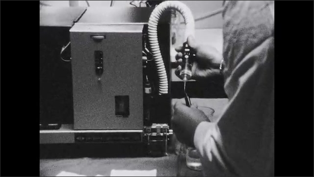 1950s: UNITED STATES: positioning of airway in patient. Scientist works in lab with machine.