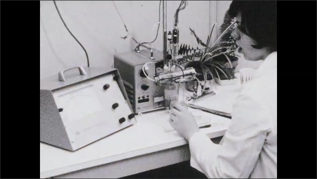 1950s: UNITED STATES: lady flicks switch on machine. Lady in science research lab. Insertion of grabber into tube