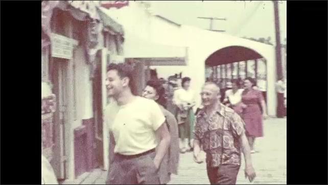 1940s: CALIFORNIA, UNITED STATES: duck dives in pond. People walk along sidewalk in street. People on beach. Ladies walk together.