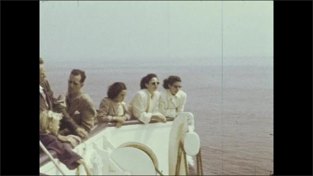 1940s: On a boat traveling through harbor canal. People on boat. People along side of boat, watching the water as boat travels.