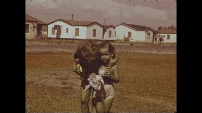 1940s: Group of people gathered around front porch of house. Two young girls play with dolls as they walk across front lawn. Woman, man and dog walk to mailbox and pose.