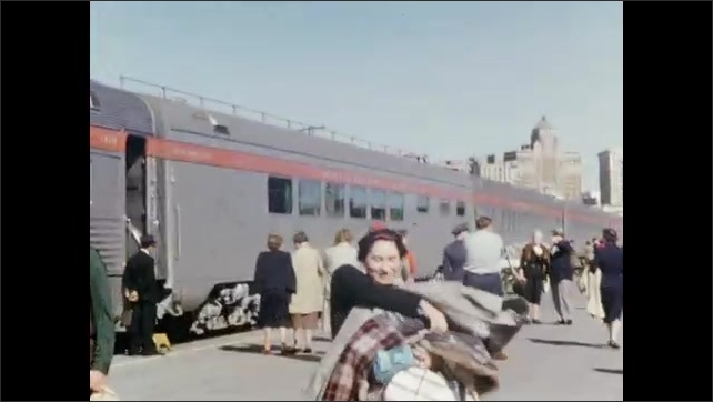 1950s: Man and woman pose in front of building. Men pose in front of building. Woman stands in front of train, gathers luggage. Woman sits at table. Man stands at railing.