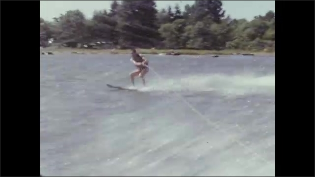 1950s: UNITED STATES: family on boat. Girl on slide by seaside. Man on water-ski behind boat.