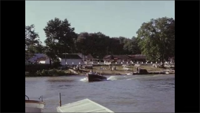 1950s: UNITED STATES: man drives motor boat. Boat in harbour. Man bring boat to mooring. Family by mooring