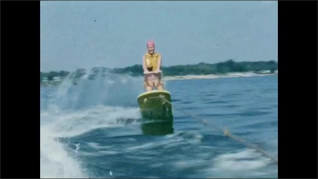 1950s: Woman in swim cap waves and smiles while wakeboarding behind a boat.
