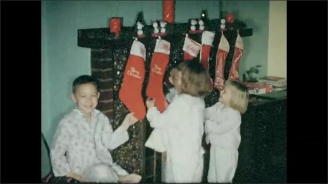 1950s: Four children in pyjamas hang Christmas stocking on the fireplace. Mother hangs the two adult stockings. Four children pose beneath their stockings. Christmas cards hung on the stairwell.