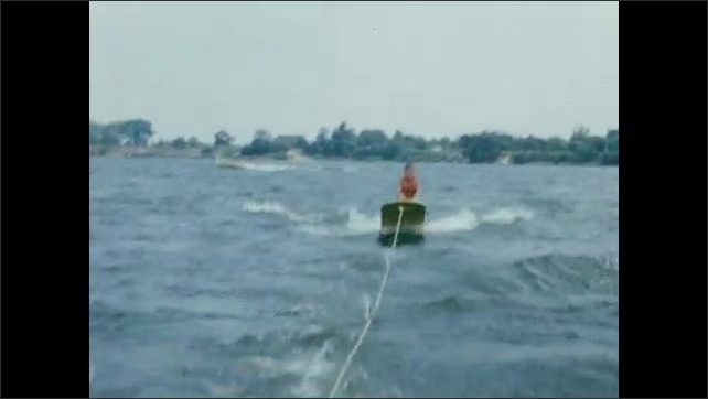 1950s: Man waterskis in lake. Boy on wakeboard on lake. Boy waves from wakeboard behind boat.