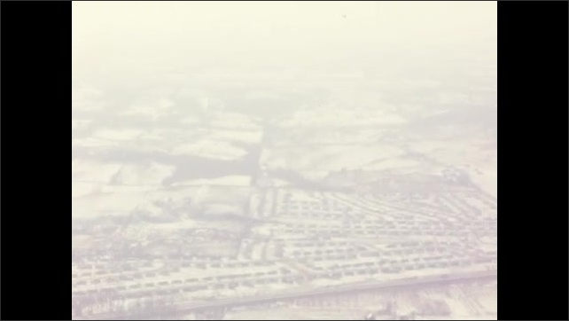 1960s: Car drives along.  Mountains.  River.  Town.  Roads.  Airplane wing.